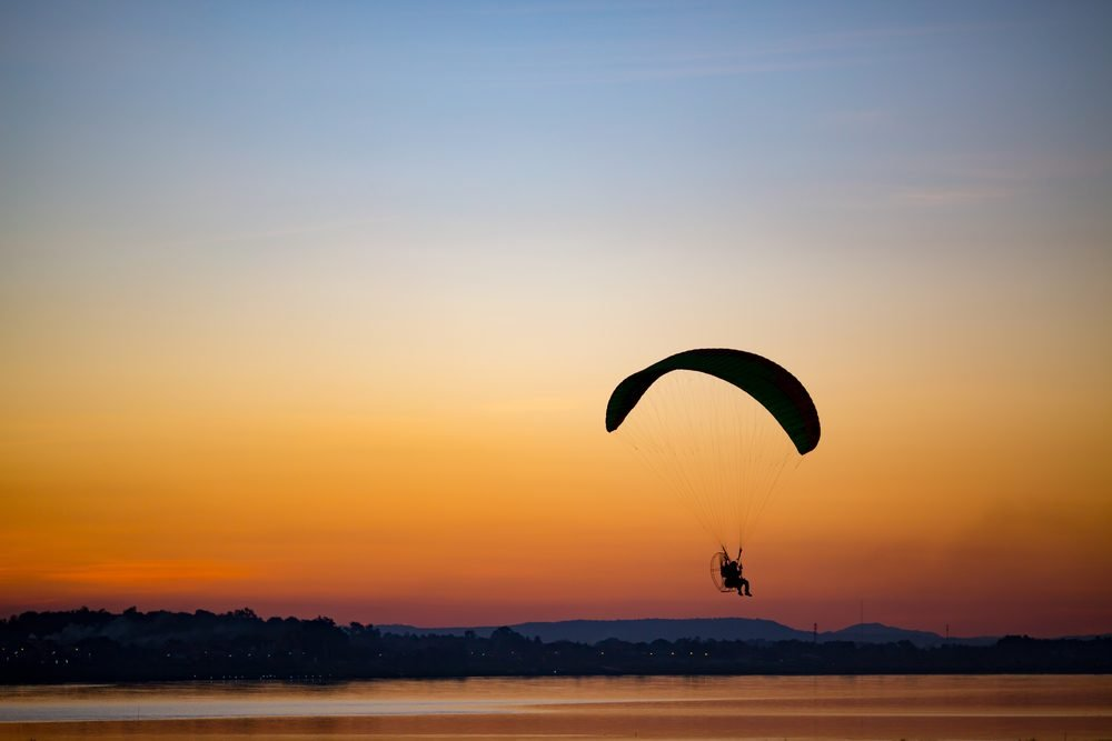 Silhouette of paramotor flying at orange sunset