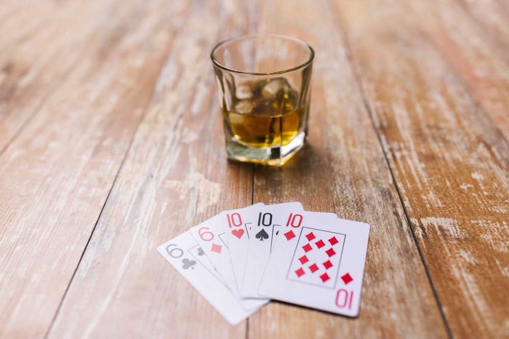 gambling, fortune and entertainment concept - glass of whisky and playing cards on table
