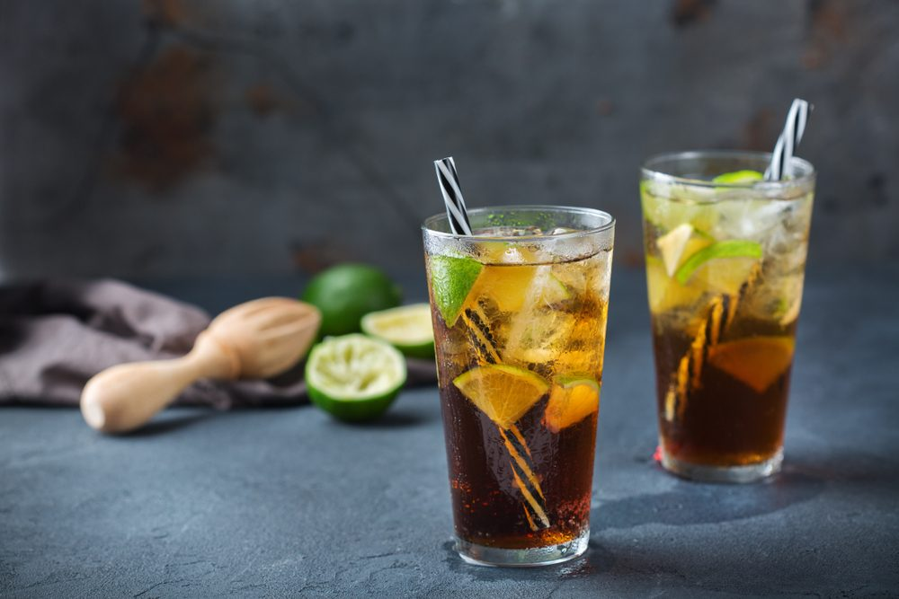Food and drink, holidays party concept. Cuba libre or long island iced tea alcohol cocktail drink beverage, longdrink in a glass with straw, ice and lime on a dark table
