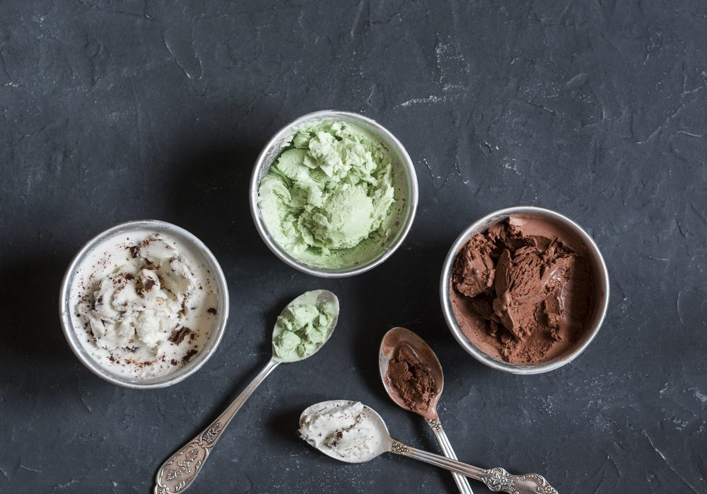 Range of coconut milk ice cream with chocolate, matcha powder, chocolate chips and vanilla. On a dark background, top view. Gluten free vegetarian dessert
