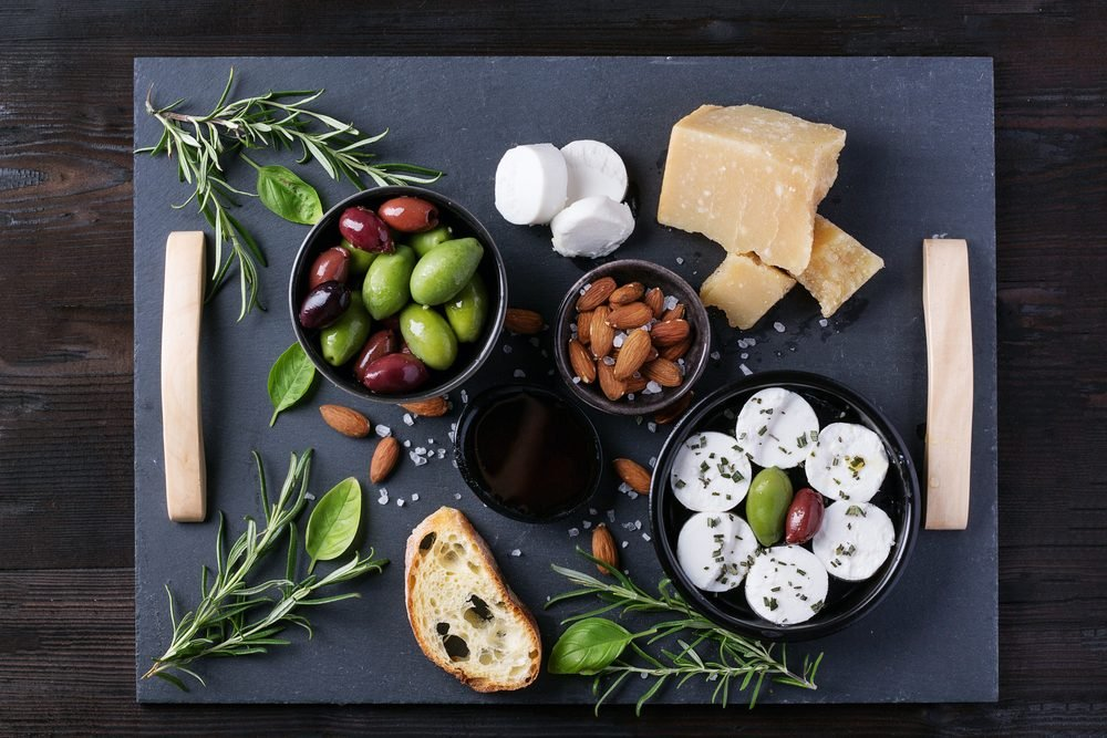A set of Italian appetizers: salami and goat cheese, served with bread, olives, olive oil and wine decorated with napkin. Top View