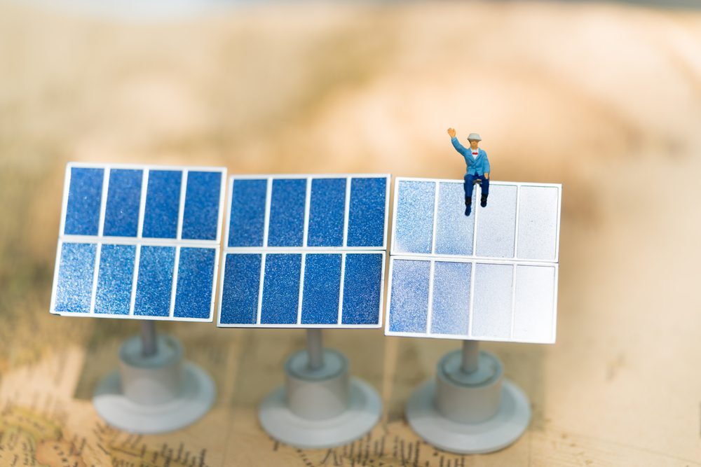 Miniature people: Worker sitting on solar cell with vintage world map using for technology nature ecology power.