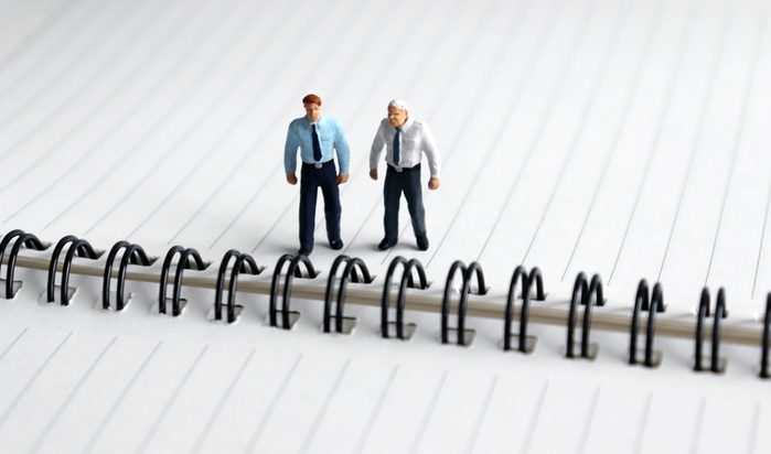 Miniature people standing on open notes.
