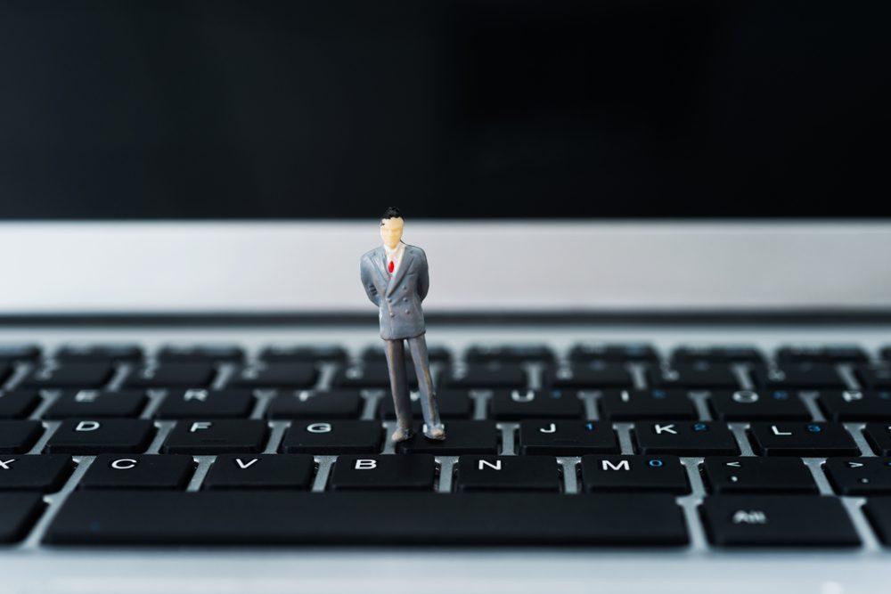 Miniature businessman standing on laptop keyboard.