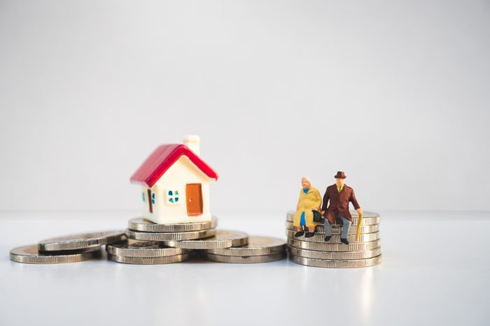 Miniature elderly people sitting on stack coins and mini house using as job retirement, business and insurance concept