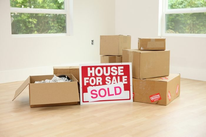 Cardboard boxes and real estate sign