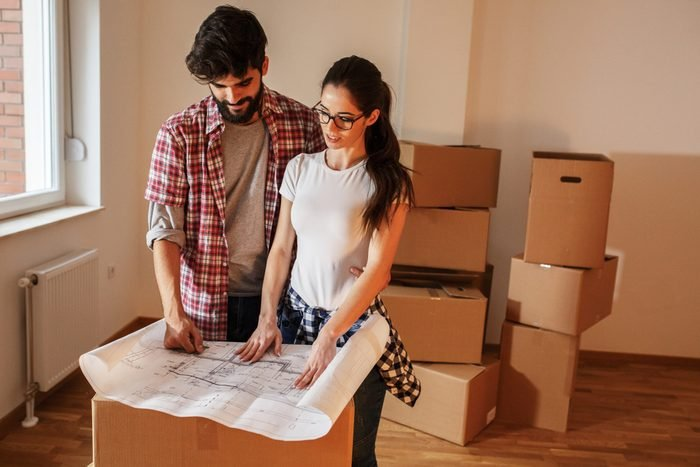 Young couple moving into a new house.They unpacking and planing to buy new furniture.