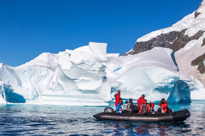 Boat full of tourists explore huge icebergs drifting in the bay near Cuverville island, Antarctic peninsula
