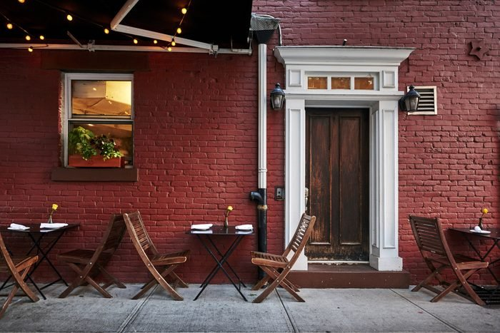 a colorful brick building with tables and chairs in an iconic neighborhood of Brooklyn, New York City