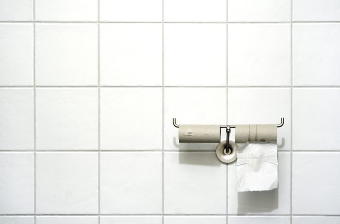 Toilet paper holder with two rolls, one empty, one with a single sheet