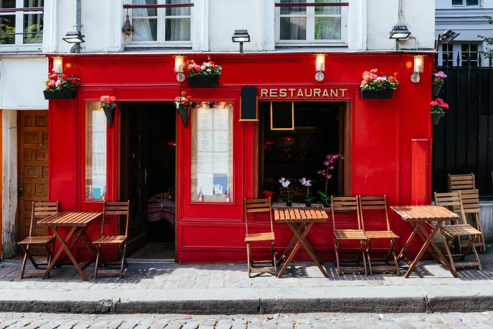 View of street with tables of cafe in quarter Montmartre in Paris, France. Cozy cityscape of Paris. Architecture and landmarks of Paris