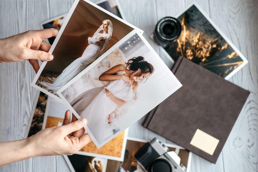 Printed wedding photos with the bride and groom, a vintage black camera, photoalbum and woman hands with two photos
