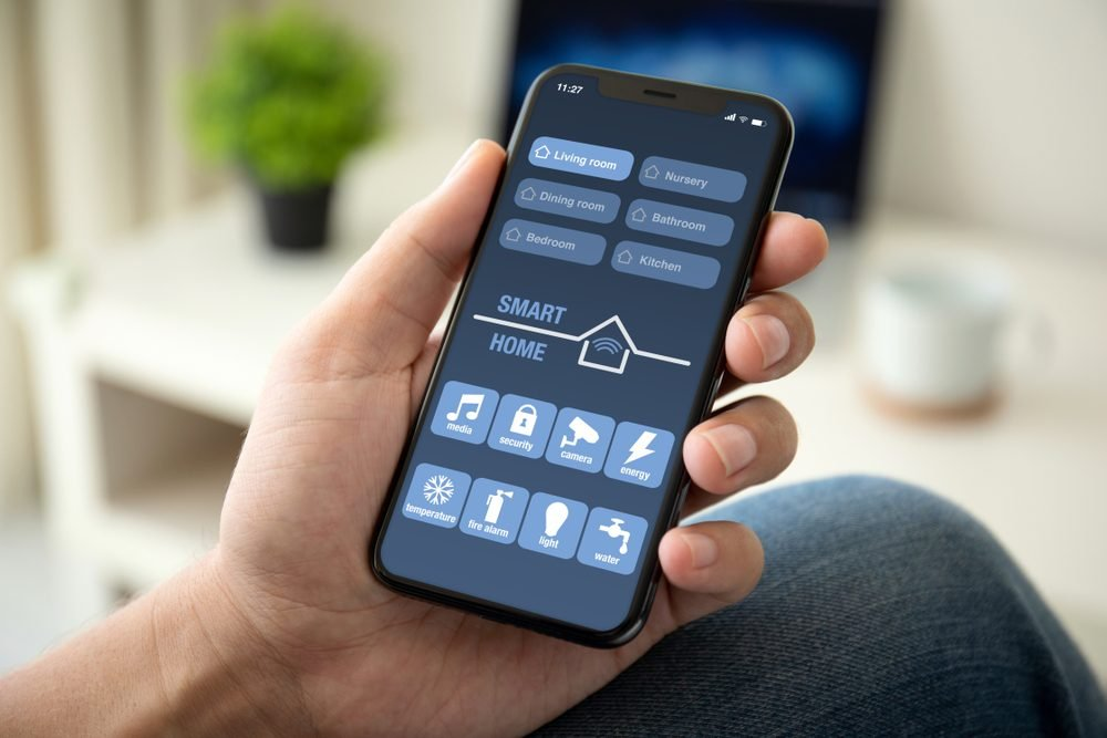 man hand holding phone with app smart home in room house