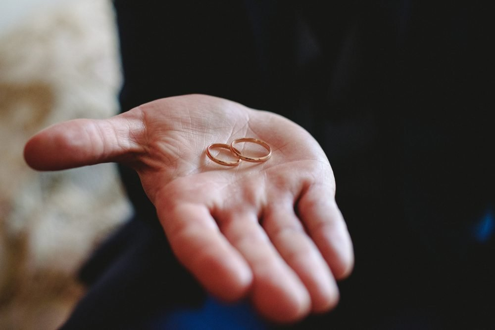 Simple gold wedding rings fastened in the palm of the groom's hand