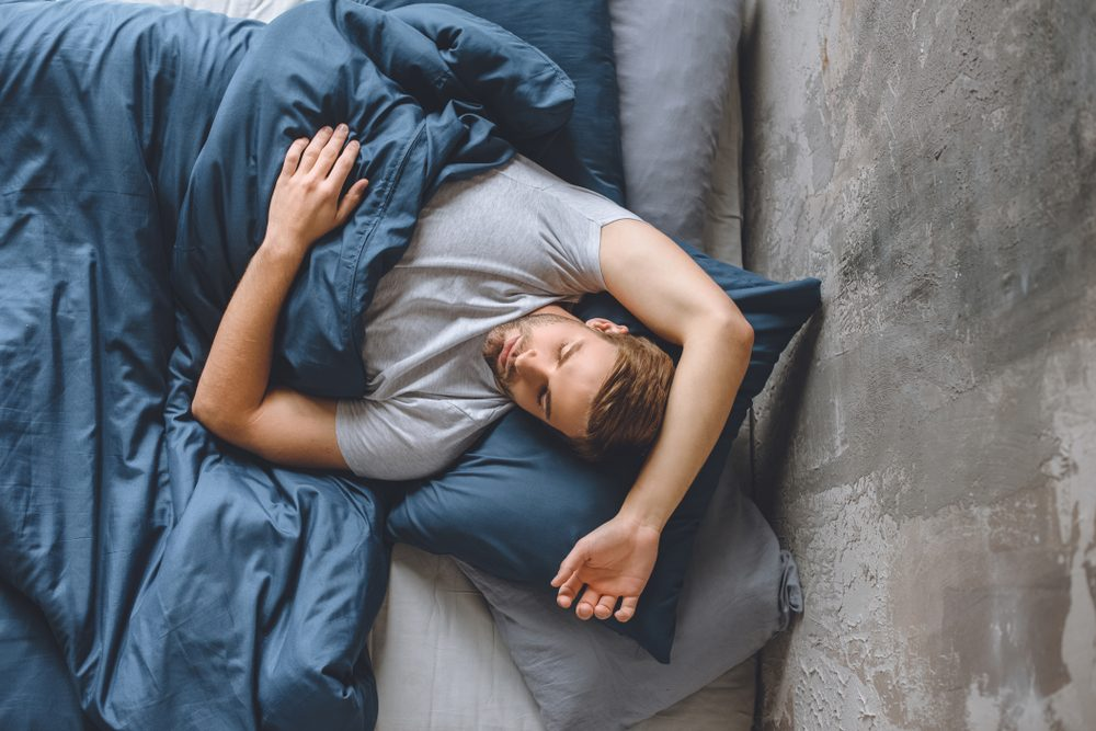 elevated view of young handsome man sleeping under blanket in his bed at home