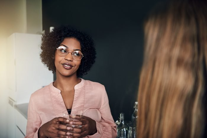 Smiling African businesswoman talking with a female business colleague while taking a break together in a modern office