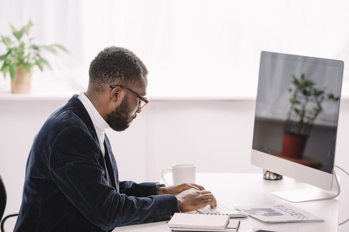 focused african american businessman typing on computer keyboard in office