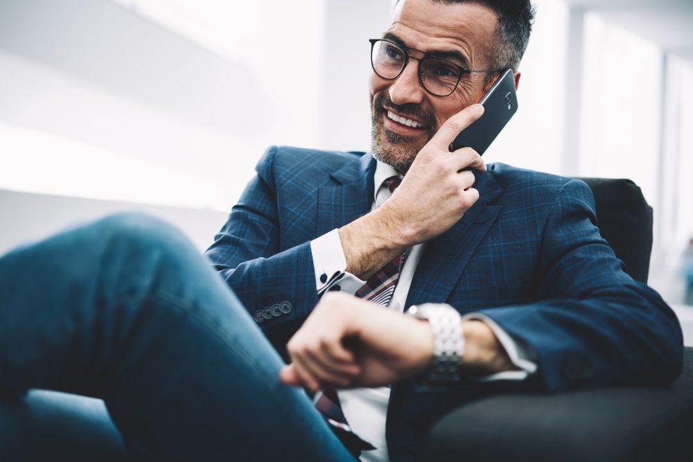 Successful entrepreneur middle aged laughing during phone conversation on smartphone sitting in office.Prosperous businessman in formal wear calling on cellphone.Cheerful proud ceo talking on cellular