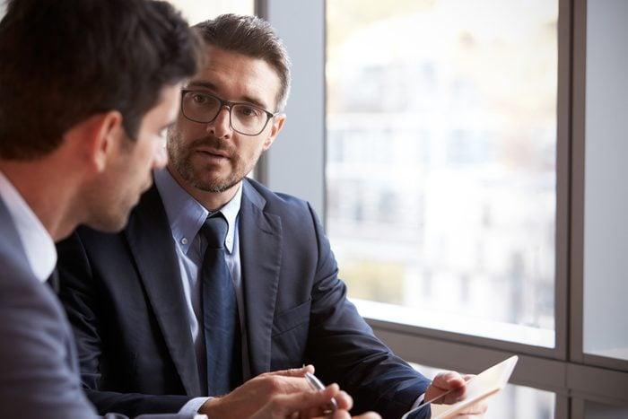 Two Businessmen Using Digital Tablet In Office Meeting