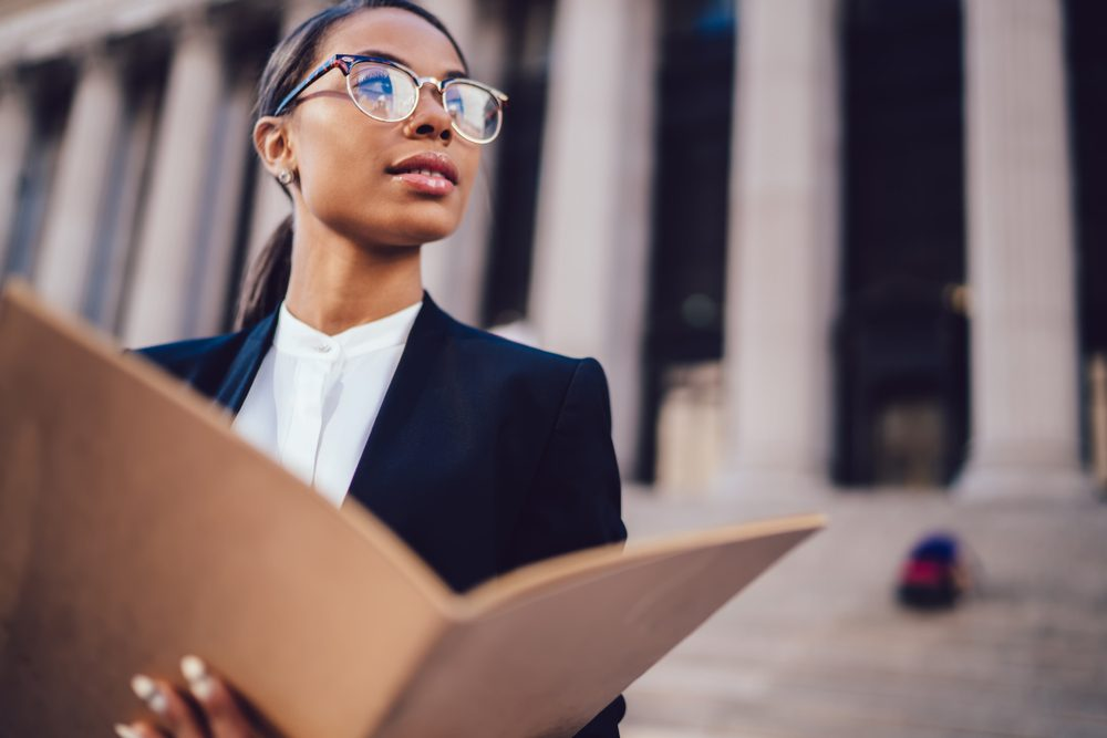 Thoughtful African American businesswoman in optical spectacles holding documents looking away while standing in urban setting with copy space. Female dark skinned student of high economic university