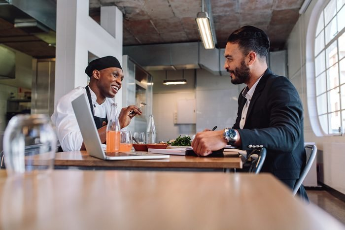 Restaurant business manager sitting and talking with chef. Restaurant owner having a conversation with employee.