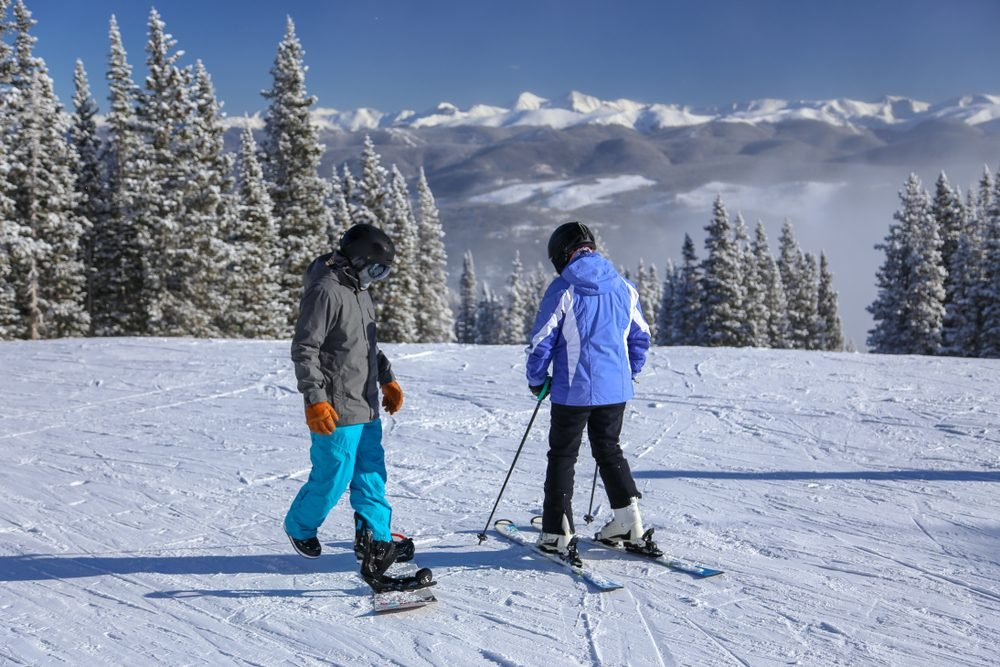 Skier and snowboarder in the winter snow in Breckenridge Colorado ski resort with the Rocky Mountains in the background