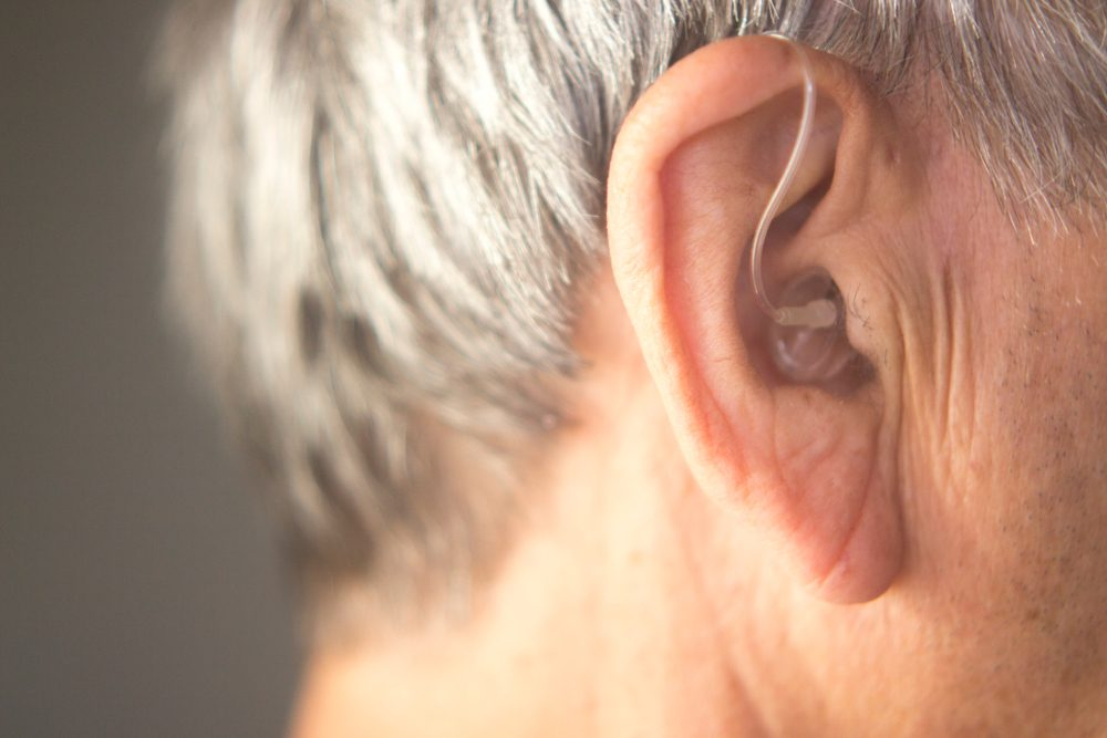 Digital modern hearing aid in the ear of aged old man.