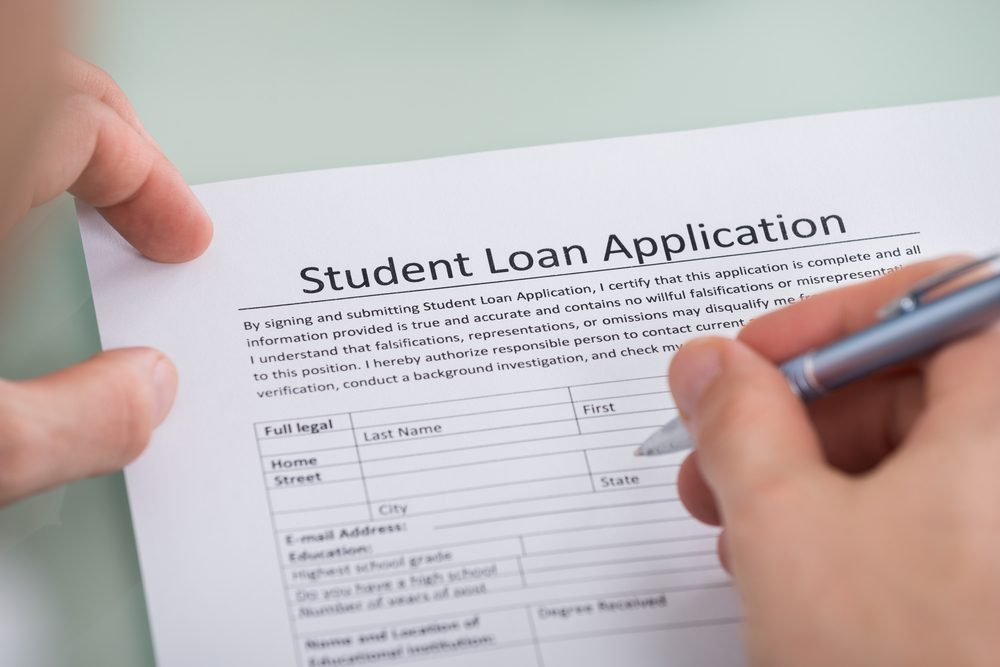 Close-up Of Person Hand Over Student Loan Application Form