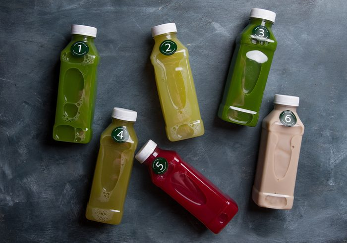 Healthy eating, drinks, diet and detox concept - close up of eight plastic bottles with different fruit or vegetable juices for detox plan