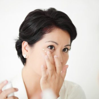 Beautiful female applying facial treatment or cream around her eyes.