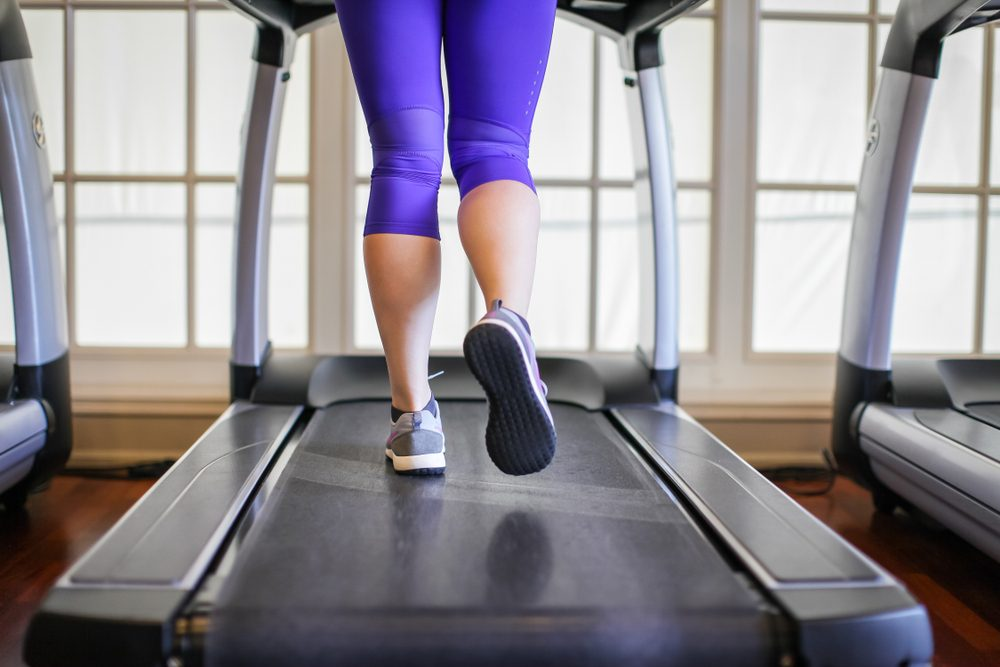 legs of woman running on treadmill in the gym which runner athletic by running shoes. Health and sport concept background, Healthy lifestyles