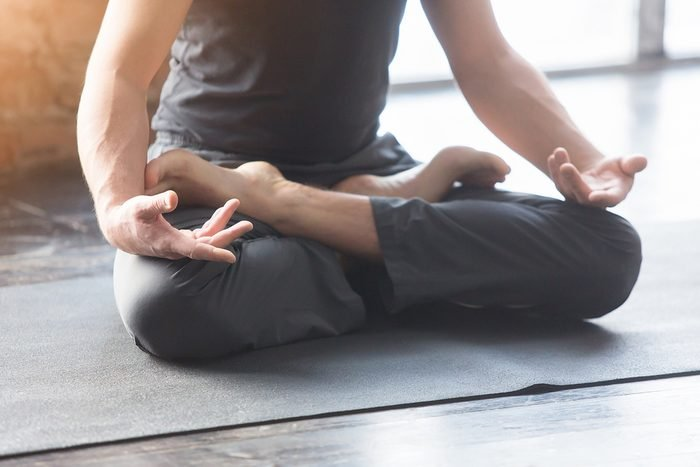Close up men hands. Young men do yoga indoors on black mat. Guy exercising yoga with a black background in gym. Young men meditating in lotus posture closeup