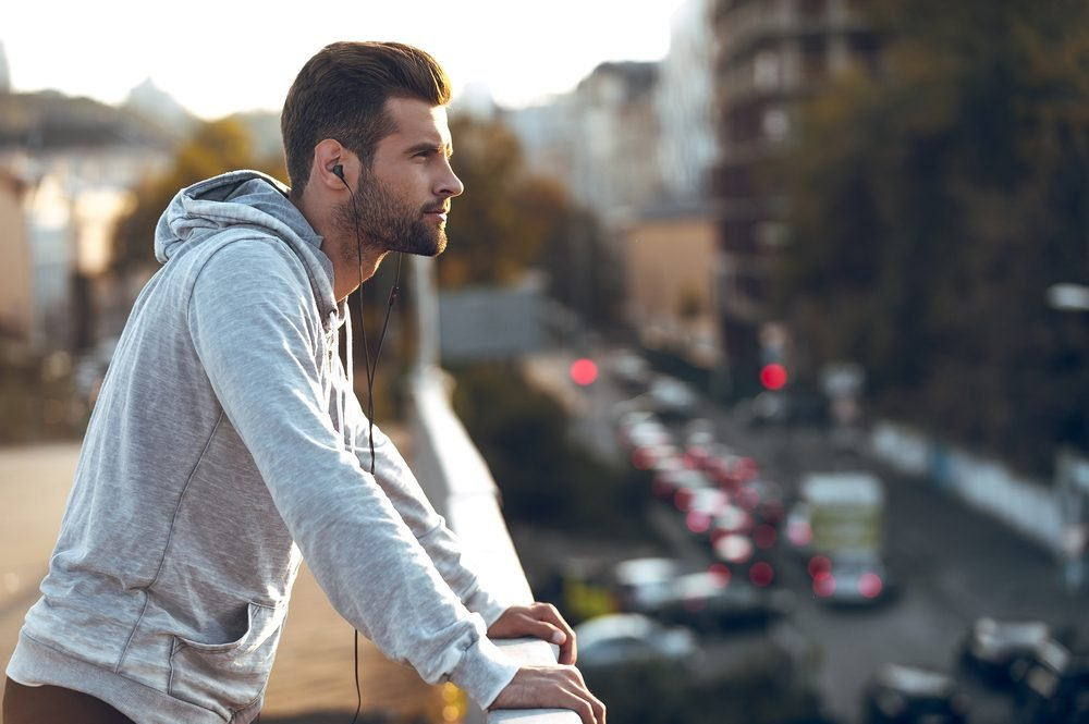In love with his city. Side view of pensive young man in headphones looking away while standing on the bridge