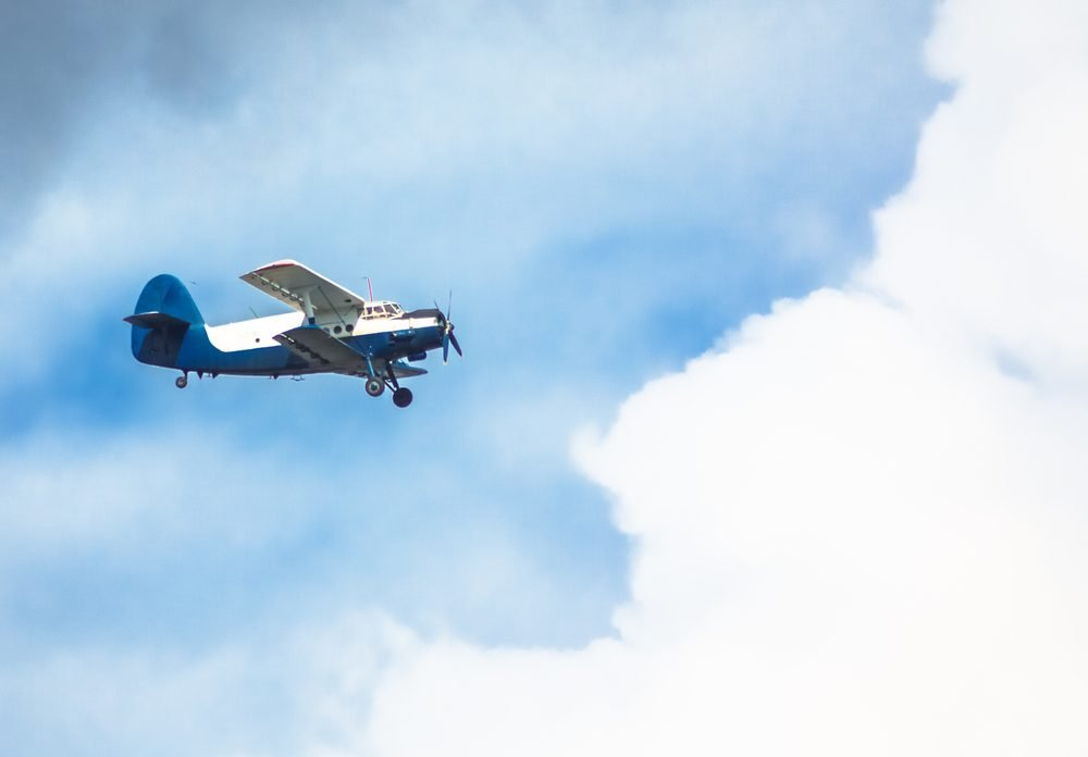 Biplane in blue Sky over clouds