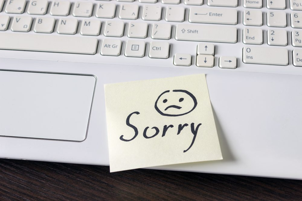Handwritten note is on the keyboard. - Sorry. Sad smiley face drawn in black.