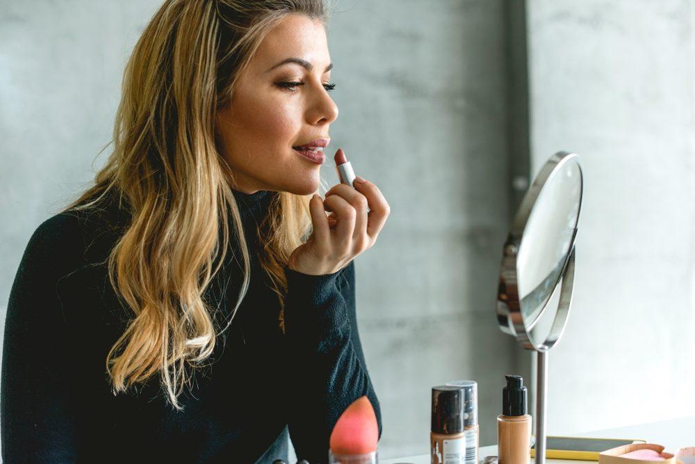 Beautiful woman Putting lipstick