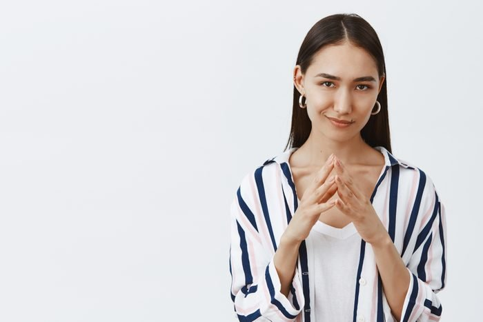 I have great evil plan. Good-looking confident and tricky woman in striped blouse, holding fingers together and smirking at camera, having some bad intention in mind, planning to commit crime