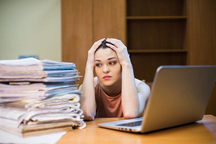 A young woman sits in front of a pile of papers and a computer holding her head