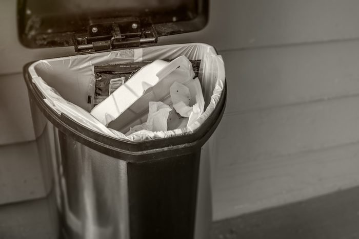 Trash concept with waste bin open and full of garbage. Gross and smelly, black and white and sepia toned HDR image with copy space.