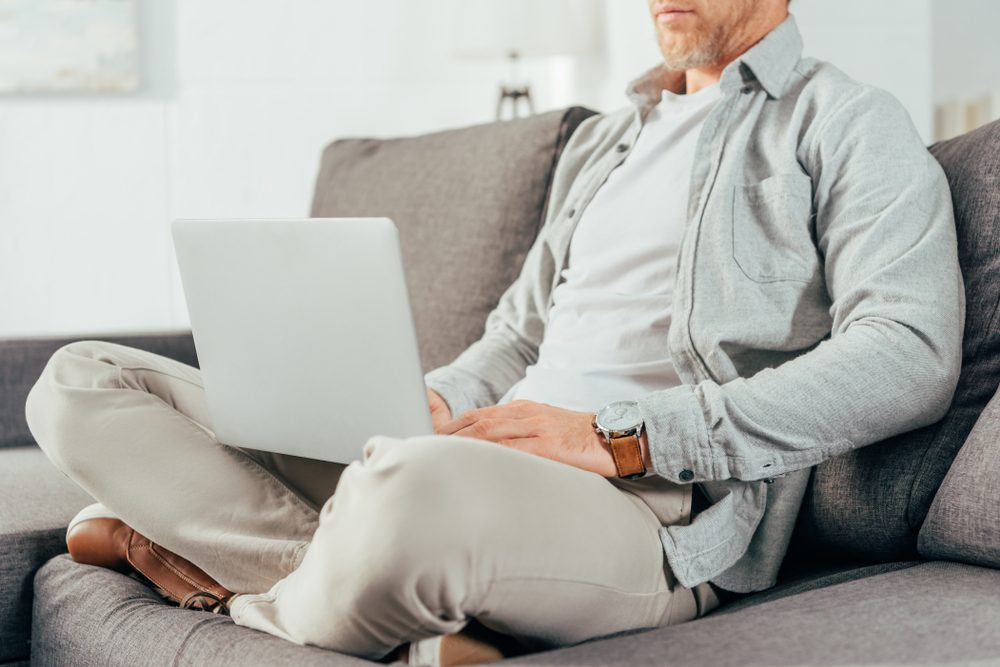 cropped shot of man sitting on couch and using laptop