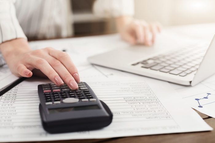 Young woman managing finances, reviewing bank account on laptop and calculator, paying taxes online, copy space