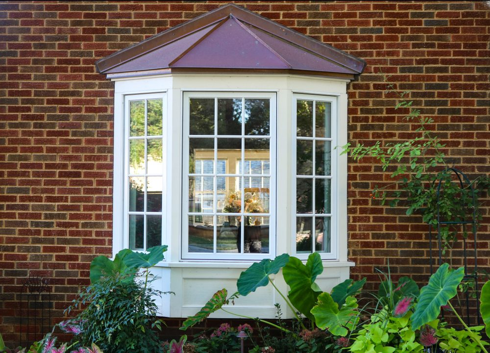 Bay window in a brick house with reflection of trees and view of windows and flowers inside and flowers and elephant ears outside