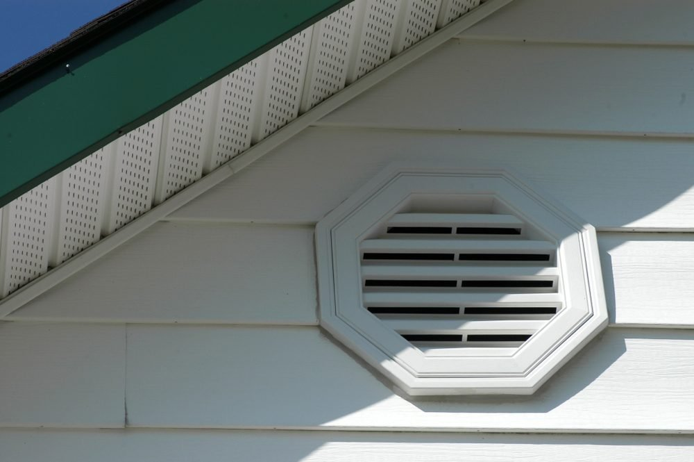 Close up of white exterior home detail of white vinyl siding and white vent with white soffit and dark green fascia, and a hint of blue sky on a sunny day.