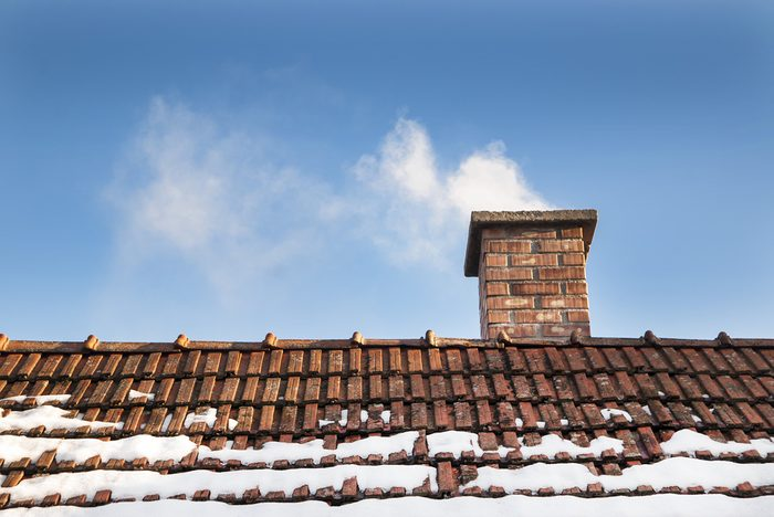 Smoke raising from a chimney in winter