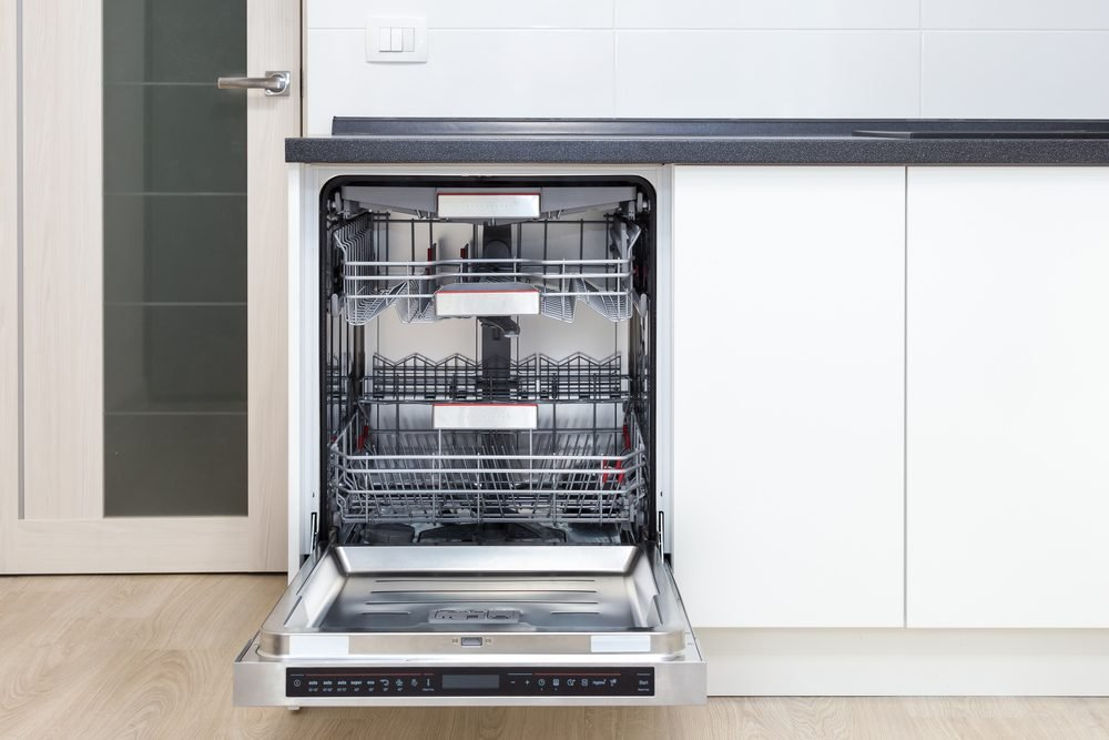 Build-in dishwasher with opened door in a white kitchen