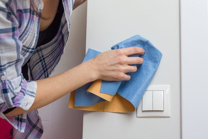 Female cleans a dirty wall at home with professional rag.