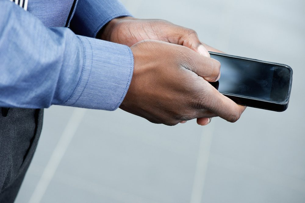 Side body of african businessman using mobile phone