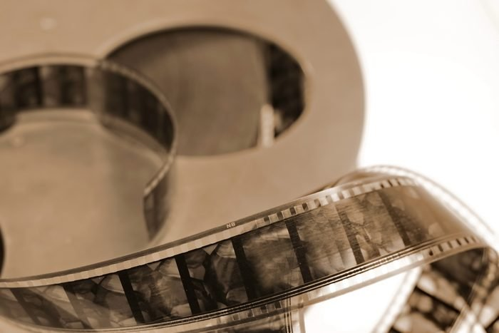 Old cine-film. Film strip on a blur background. Sepia photo.
