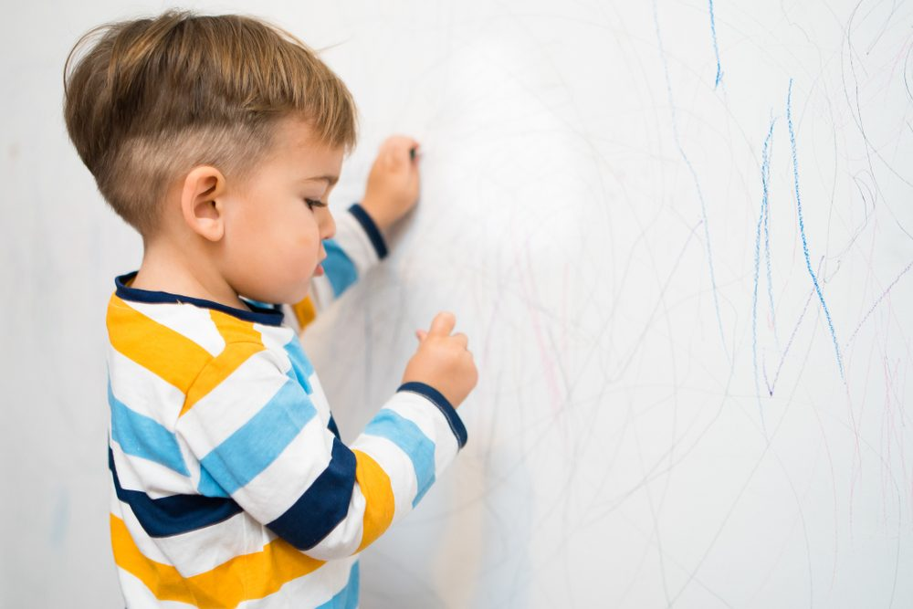 Little Boy drawing on the Wall