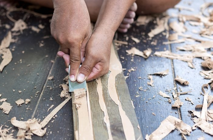 Hands striping glue from parquet wood flooring